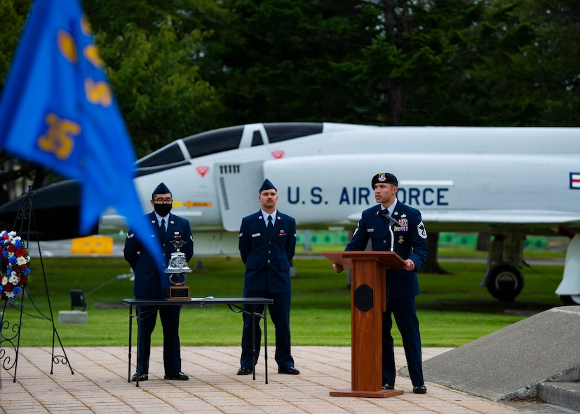 Military member in uniform gives a speech at a podium.