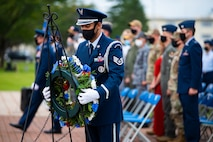 Military member in uniform picks up a wreath.