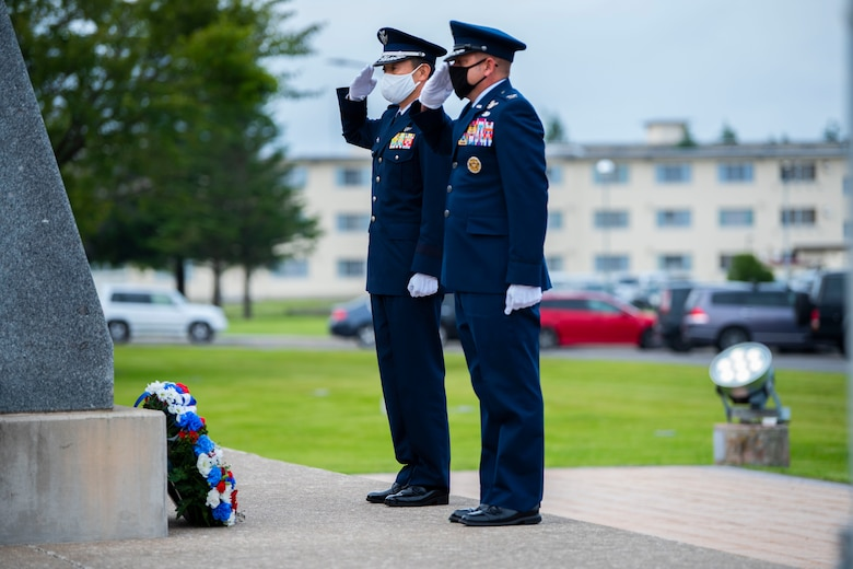 Military member in uniform salute to a wreath placed on the ground.