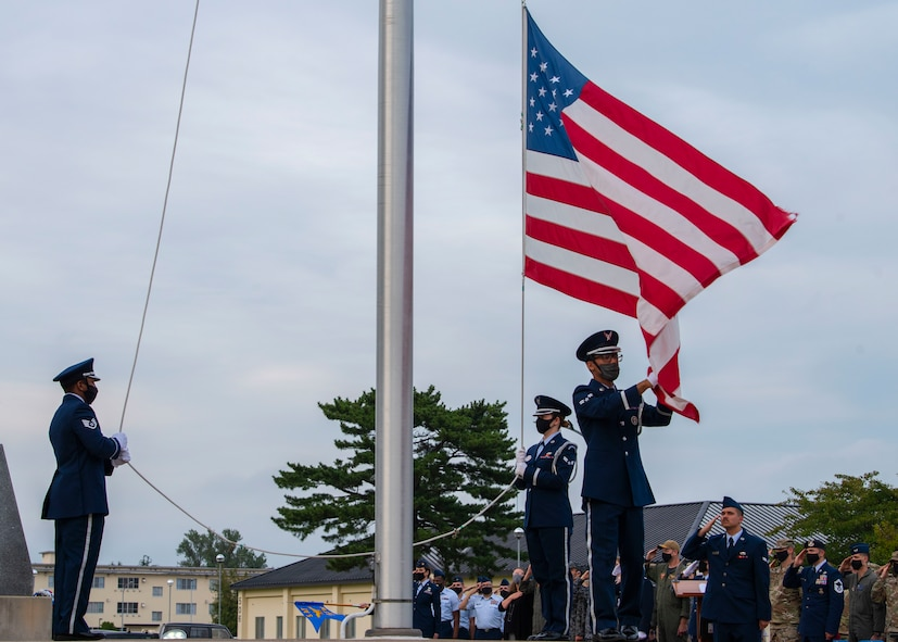 Military members in uniform lower an American flag.