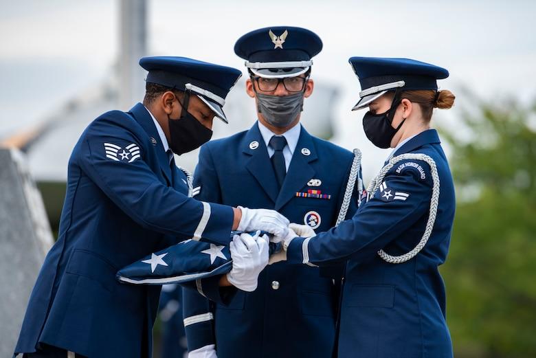 Military members in uniform fold an American flag.