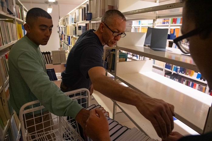 (Sept. 6, 2021) Quartermaster 3rd Class Carlos Paredes, Lt. Carl Scroggs, and Machinist Mate 3rd Class Tai Tran, left to right, assigned to the Arleigh Burke-class guided-missile destroyer USS Arleigh Burke (DDG 51) organize books during a community relations event at the National Library of Estonia while the ship is in port in Tallinn, Estonia, Sept. 6, 2021. Arleigh Burke, forward-deployed to Rota, Spain, is on its first patrol in the U.S. Sixth Fleet area of operations in support of U.S. national security interests and regional allies and partners in Europe and Africa.