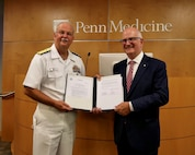 US Navy Surgeon General RADM Bruce Gillingham and Kevin Mahoney, Chief Executive Officer for the University of Pennsylvania Health System, hold the signed agreement that starts a three-year partnership to integrate members of the Navy with the Trauma Division at Penn Presbyterian Medical Center (PPMC). The program, known as Naval Strategic Health Alliance for Readiness and Performance is designed to provide sustained experiences in all aspects of trauma care – from surgery to anesthesiology to nursing – in one of the nation's busiest trauma centers. (U.S. Navy photo by Captain John Gay)