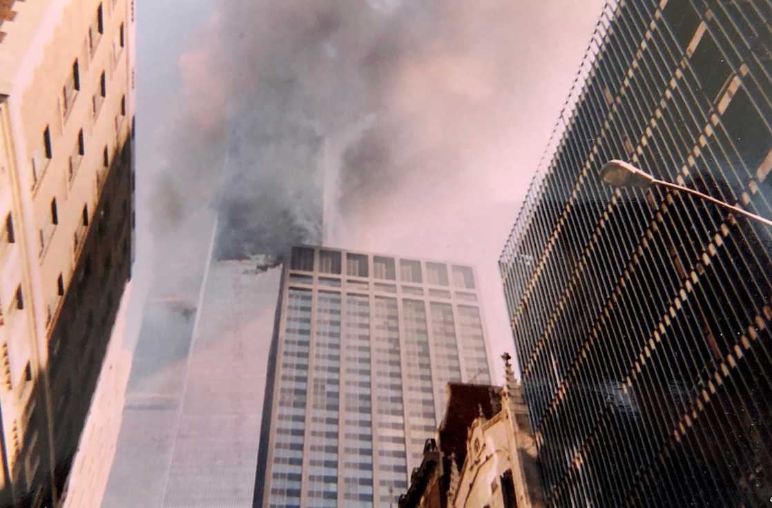 Smoke and flames come from the Twin Towers Sept. 11, 2001, at the World Trade Center, New York City, New York. This photo was captured with a disposable camera purchased specifically to capture events as they unfolded in front of Col. Ephod Shang, vice commander of the 367th Recruiting Group and deputy director at the AFRC Headquarters for Recruiting on Robins AFB, Georgia, when he was a newly minted captain at the time. (Courtesy photo by Col. Ephod Shang)