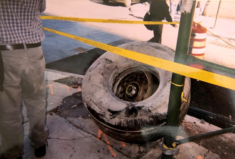 A tire from one of the aircraft that flew into one of the Twin Towers is cordoned off Sept. 11, 2001, in the street in front of the World Trade Center, New York City, New York. Col. Ephod Shang, vice commander of the 367th Recruiting Group and deputy director at the Air Force Reserve Command headquarters for Recruiting on Robins AFB, Georgia, ran towards the Twin Towers after seeing the smoke from the first crash to help people and photograph the events around him which he saw as a priority from his experience as a Reserve Citizen Airman intelligence officer. (Courtesy photo by Col. Ephod Shang)