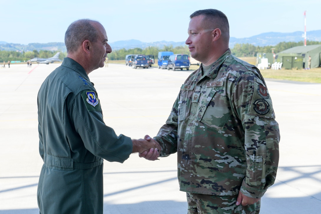 U.S. Air Force Gen. Jeff L. Harrigian, U.S. Air Forces in Europe and Air Forces Africa commander, coins U.S. Air Force Master Sgt. Corey March, 555th Aircraft Maintenance Unit production superintendent, during exercise Agile Wyvern at Cerklje ob Krki Air Base, Slovenia, Sept. 9, 2021. While visiting, Harrigian received an Agile Combat Employment tour, conducted a coin recognition ceremony and toured the base. (U.S. Air Force photo by Senior Airman Brooke Moeder)