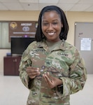 Staff Sgt. Shenika Marable, an equal opportunity leader for Task Force Spartan and 29th Infantry Division, shows off a coin she received in commemoration of her honor graduate status from the Equal Opportunity Leaders Course she recently attended. (U.S. Army photo by Staff Sgt. True Thao)