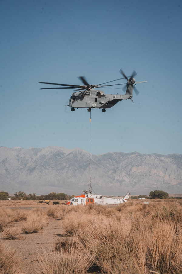A Marine Corps CH-53K King Stallion lowers a Navy MH-60S Knighthawk Helicopter to the ground after recovering it from the nearby mountain ranges after it conducted a hard landing near, Bishop, California, Sept. 5, 2021. The two day operation was the first official fleet mission for the CH-53K King Stallion, as it is currently undergoing an operational assessment while the Marine Corps modernizes and prepares to respond globally to emerging crises or contingencies. (U.S. Marine Corps photo by Lance Cpl. Colton Brownlee)