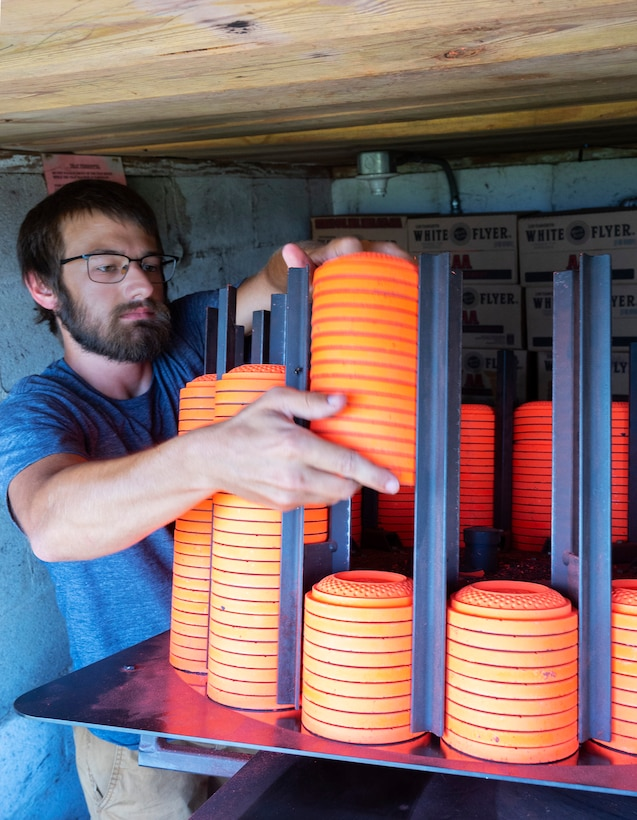 David Miotke, who works at the 88th Force Support Squadron's Rod and Gun Club, loads clay pigeons into the machine that will fling them downrange  from a trap house at Wright-Patterson Air Force Base, Ohio, Aug. 24, 2021. A round of skeet or trap shooting includes 25 attempts at the flying disks. (U.S. Air Force photo by R.J. Oriez)
