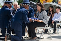 Air Force Chief of Staff Gen. CQ Brown Jr. presents the U.S. flag to retired Col. Richard E. Cole's daughter, Cindy Chal, during his interment ceremony.