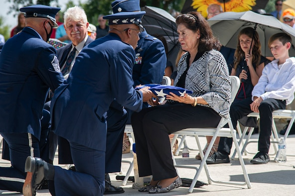 Air Force Honor Guard members fold the U.S. flag during the interment of retired Col. Richard E. Cole.