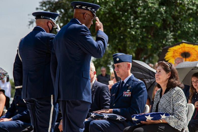Air Force Chief of Staff Gen. CQ Brown Jr. presents the U.S. flag to retired Col. Richard E. Cole's daughter, Cindy Chal, during his interment ceremony, Sept. 7, 2021.