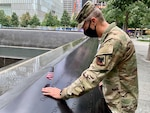 """Army Gen. Daniel Hokanson, chief, National Guard Bureau, places a flag and pauses to remember U.S. Military Academy classmate Douglas Gurian, among the almost 3,000 names engraved in the 9/11 Memorial. """"It was an attack on our nation, and deeply personal to so many of us,"""" Hokanson said. The National Guard transformed from a strategic reserve to an operational force after the Sept. 11, 2001, attacks. This image was acquired using a cellular device."""