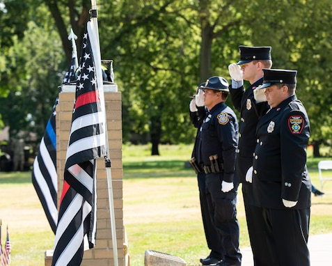 Local firefighters and police officers salute after placing their headgear and flags on each pillar of the 9/11 Memorial during a remembrance ceremony held at Rock Island Arsenal Sept. 10.