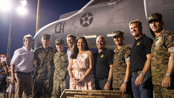 """U.S. Marines, veterans and families pose in front an AV-8B Harrier during a dedication ceremony at the open air museum on Marine Corps Air Station Yuma, Ariz., Aug. 19, 2021. Marines from 3rd Marine Aircraft Wing and across the Marine Corps participated in a ceremony unveiling and dedicating an AV-8B Harrier at the museum to the late Lt. Col. Christopher """"Otis"""" Raible and Sgt. Bradley Atwell, whom gave their lives defending the aircraft as well as surrounding Marines during an attack on Camp Bastion, Afghanistan in 2012."""