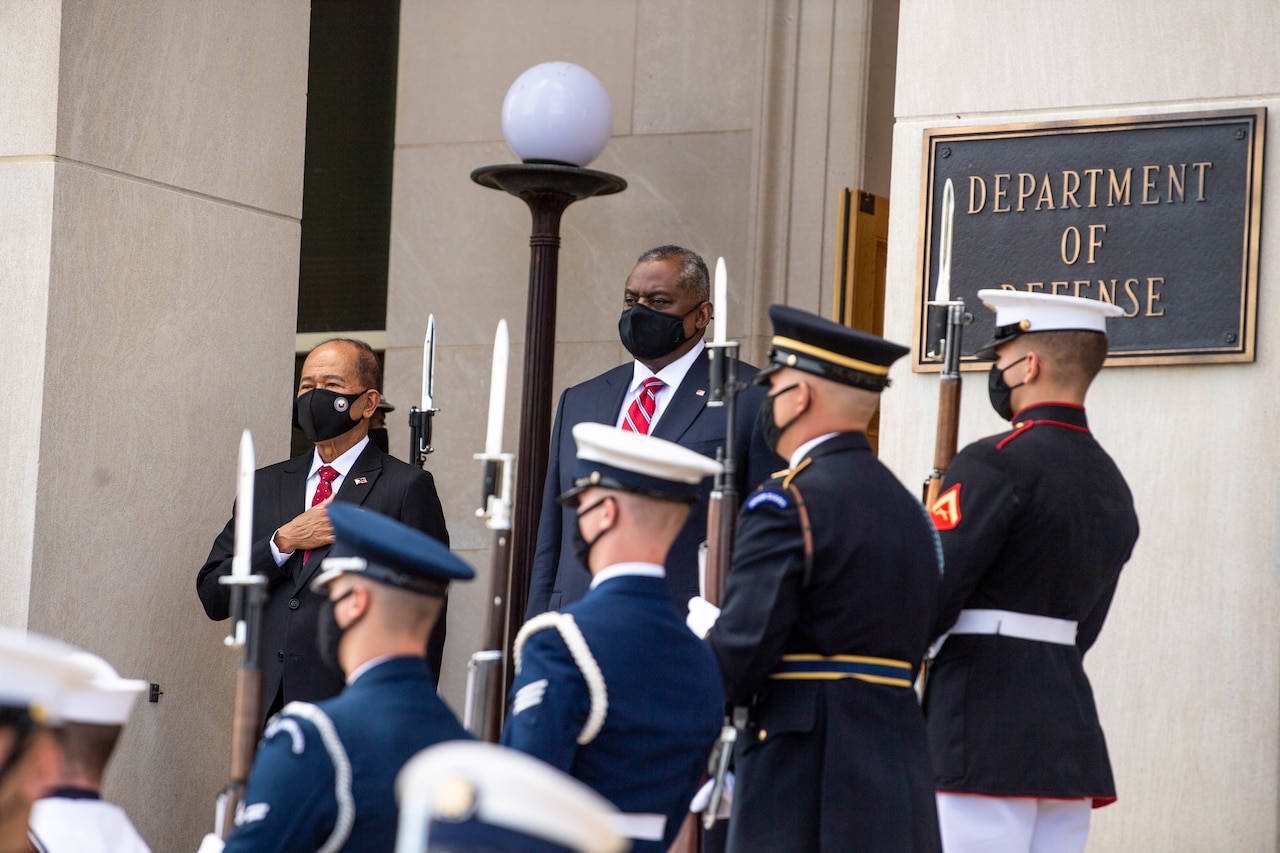 Two men stand at attention. A military honor guard is in the foreground.