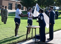 The 11th Wing and Joint Base Anacostia-Bolling Command Team, Command Chief Master Sgt. Christy Peterson and Col. Mike Zuhlsdorf, hand a ceremonial baton and flag to Staff. Sgt. Bryan Potter, 794th Communication Squadron, and 1st Lt. Hillary Bissing, 11th Logistics Readiness Squadron, before they lead a 9/11 memorial run on Sept. 10, 2021. Mission  partners from across the National Capitol Region gathered at JB Anacostia-Bolling to honor those who died 20 years ago during the terror attacks on the World Trade Center and the Pentagon on September 11, 2001. (U.S. Air Force photo by Staff Sgt. Kayla White)