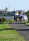 U.S. Air Force Staff. Sgt. Bryan Potter, 794th Communication Squadron, and 1st Lt. Hillary Bissing, 11th Logistics Readiness Squadron, carry a ceremonial baton and flag during a 9/11 memorial run along the Potomac River at Joint Base Anacostia-Bolling, Washington D.C. on Sept. 10, 2021. Mission partners from across the National Capitol Region gathered at JB Anacostia-Bolling to honor those who died 20 years ago during the terror attacks on the World Trade Center and the Pentagon on September 11, 2001. (U.S. Air Force photo by Staff Sgt. Kayla White)