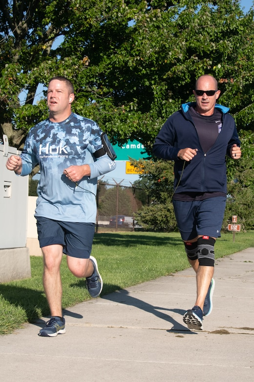 """Chief Master Sgt. David Teets, left, 436th Aerial Port Squadron chief enlisted manager, and Chief Master Sgt. Ronely Rivera-Ortiz, 436th Aerial Port Squadron  superintendent, approach the finish line during the """"I've Got Your Six"""" 5k at Dover Air Force Base, Delaware, Sept. 10, 2021. Some participants were encouraged to run in pairs while each held a cord, encouraging people to finish together. (U.S. Air Force photo by Mauricio Campino)"""