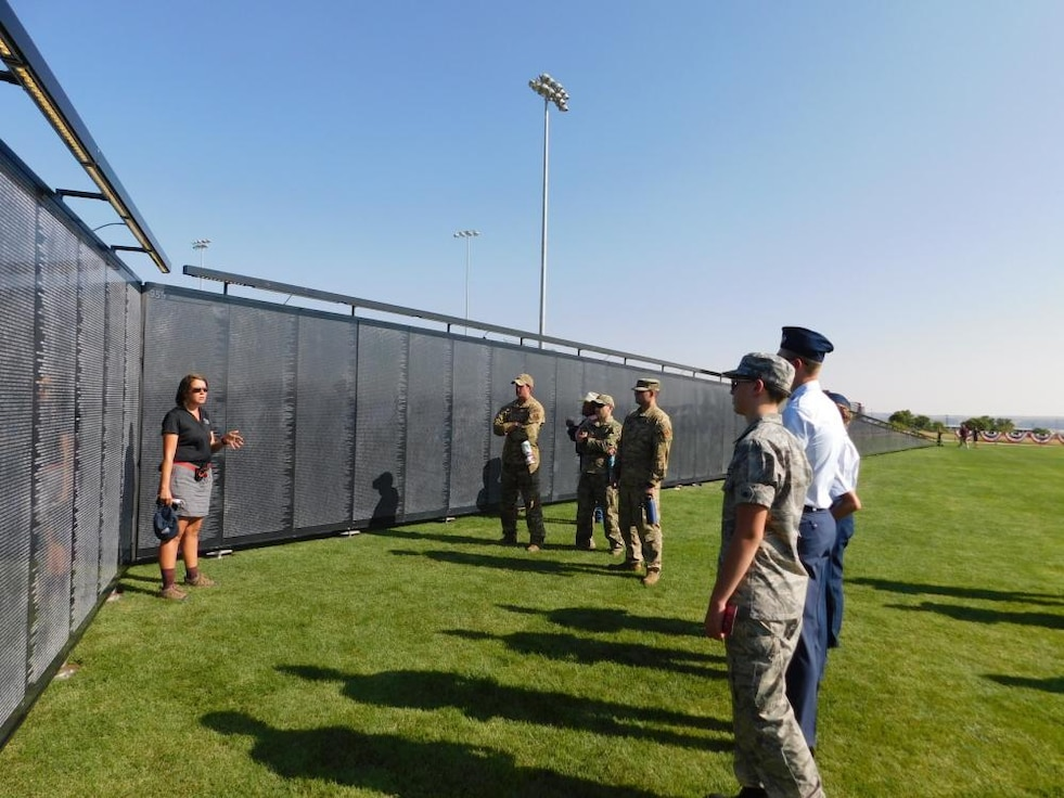 A civilian woman speaks to Airmen and cadets at a replica of the Vietnam Memorial Wall.