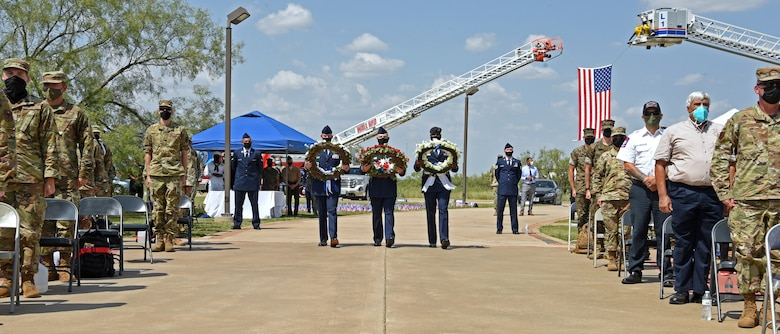 U.S. Air Force members assigned to the 17th Training Wing carry memorial wreaths during a 9/11 memorial ceremony at the Firefighter Memorial Troop Walk, on Goodfellow Air Force Base, Texas, Sept. 8, 2021. The red wreath represented the fire service and the bloodshed in the fight to save our own, the blue wreath represented the vastness it took to manage the events of 9/11, and the white wreath represented emergency medical community and all other partners and the purity of their efforts. (U.S. Air Force photo by Senior Airman Abbey Rieves)