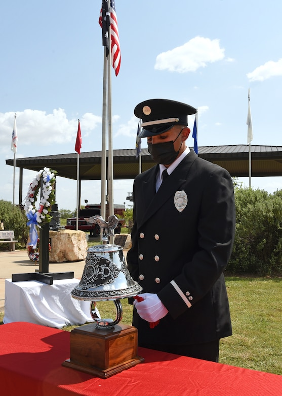 Lance Sauceda, City of San Angelo firefighter and paramedic, conducts the fireman's bell ringing at a 9/11 memorial ceremony at the Firefighter Memorial Troop Walk, on Goodfellow Air Force Base, Texas, Sept. 8, 2021. The bell was rung five times, which symbolized that a fallen firefighter's duties are over and charges living firefighters to take on the duty of protecting those left behind. (U.S. Air Force by Senior Airman Abbey Rieves)