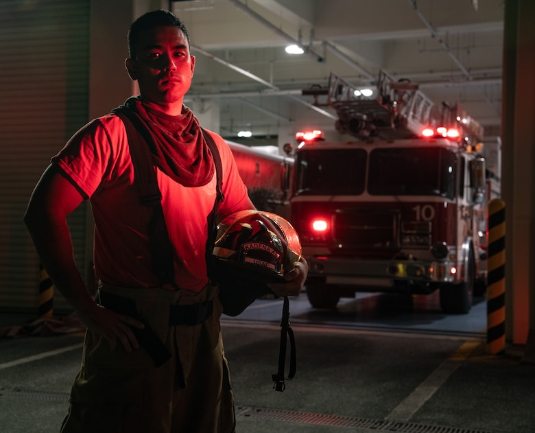 A civilian firefighter stands in front of a fire truck.
