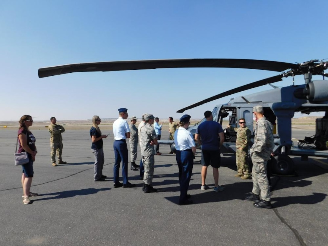 Air Force helicopter pilots speaks to people near HH-60G Pave Hawk.