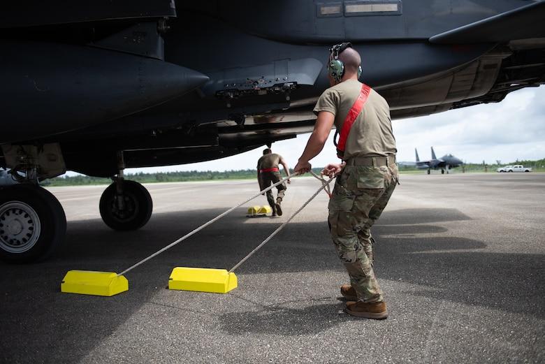 A U.S. Air Force Airmen pulls yellow chocks from underneath an F-15E Strike Eagle