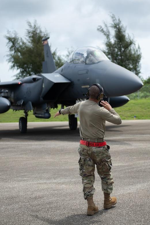 A U.S. Air Force Airmen guides a F-15E Strike Eagle on a Flight Line to park it
