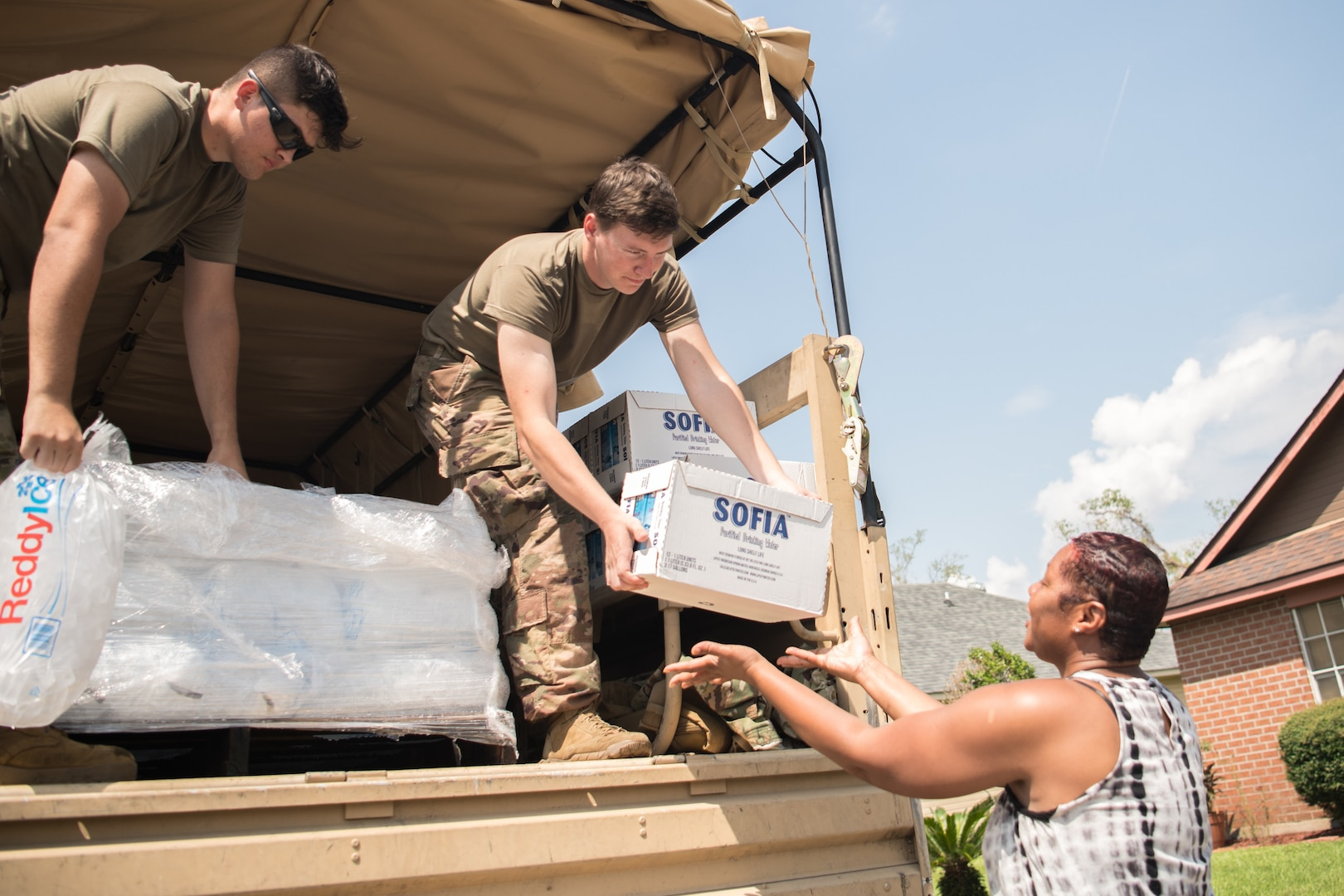 Oklahoma National Guardsmen Spc. Michael West, left, and Spc. Gage Stone, right, truck drivers with Alpha Company, 120th Engineer Battalion, 90th Troop Command, give supplies to a resident of a neighborhood in LaPlace, Louisiana, Sept. 7, 2021. Oklahoma National Guardsmen drove throughout neighborhoods to distribute supplies directly to Louisiana residents, allowing for essential aid to reach the local populace quickly. (Oklahoma National Guard photo by Senior Airman Alex Kaelke)