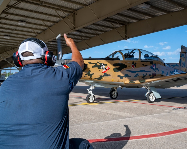 Alex Arriaga, 47th Flying Training Wing crew chief, gives a thumbs up to the pilots as they check the control surfaces of a T-6 Texan II on Laughlin Air Force Base on September 8, 2021. Flight control checks help ensure that the aircraft the pilots are flying will respond in the way they expect. (U.S. Air Force Photo by Senior Airman Nicholas Larsen)