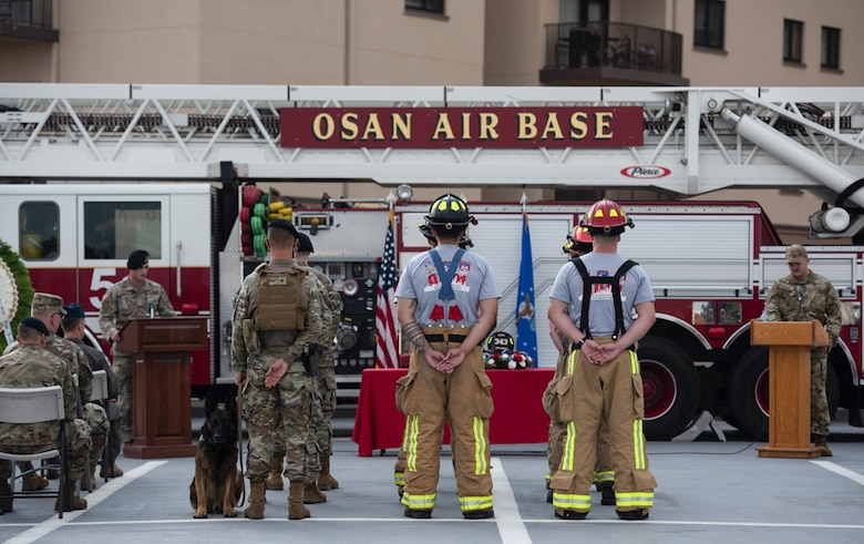 Fire fighters assigned to the 51st Civil Engineer Squadron and 51st Security Forces Squadron stand in formation to represent the volunteers that perished during a 20th Anniversary 9/11 Remembrance Ceremony at Osan Air Base, Republic of Korea, Sept. 11, 2021.