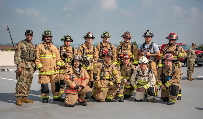 Col. Joshua Wood, 51st Fighter Wing commander, stands with fire fighters assigned to the 51st Civil Engineer Squadron before climbing 110 flights of stairs during a 20th Anniversary 9/11 Remembrance Ceremony at Osan Air Base, Republic of Korea, Sept. 11, 2021