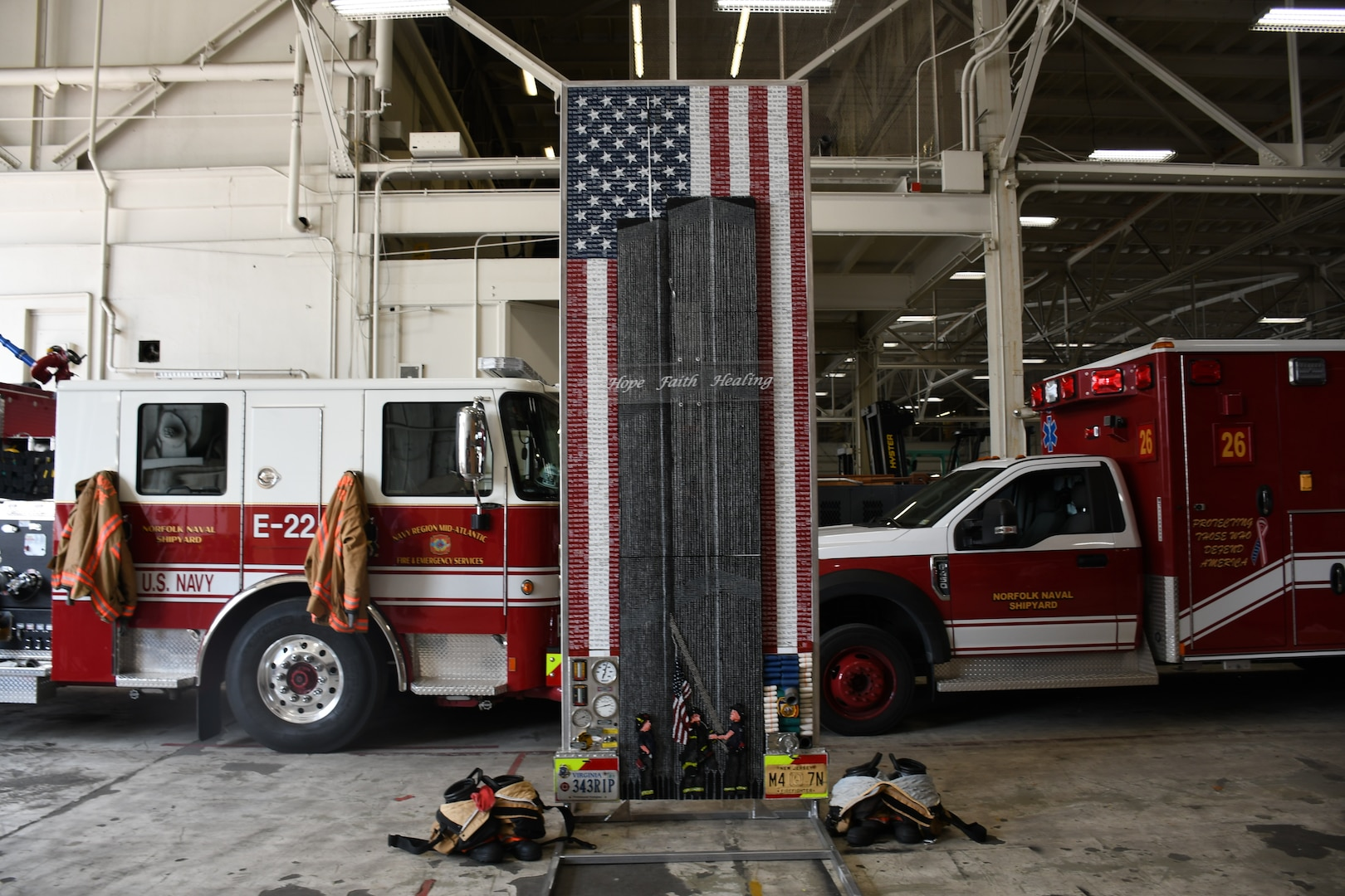"""In the Navy Region Mid-Atlantic Fire and Emergency Services firehouse aboard Norfolk Naval Shipyard (NNSY) the """"Divinity Among Heroes"""" memorial artwork stands in an ambulance bay. The tribute piece is made up of 30,000+ drywall and trim screws, 2,978 one-inch wooden blocks, the base, a simulated fire truck, is constructed of authentic gauges, cranks, handles, hoses, chevrons, and plates from a decommissioned fire truck and it stands 12 foot tall by four foot wide."""