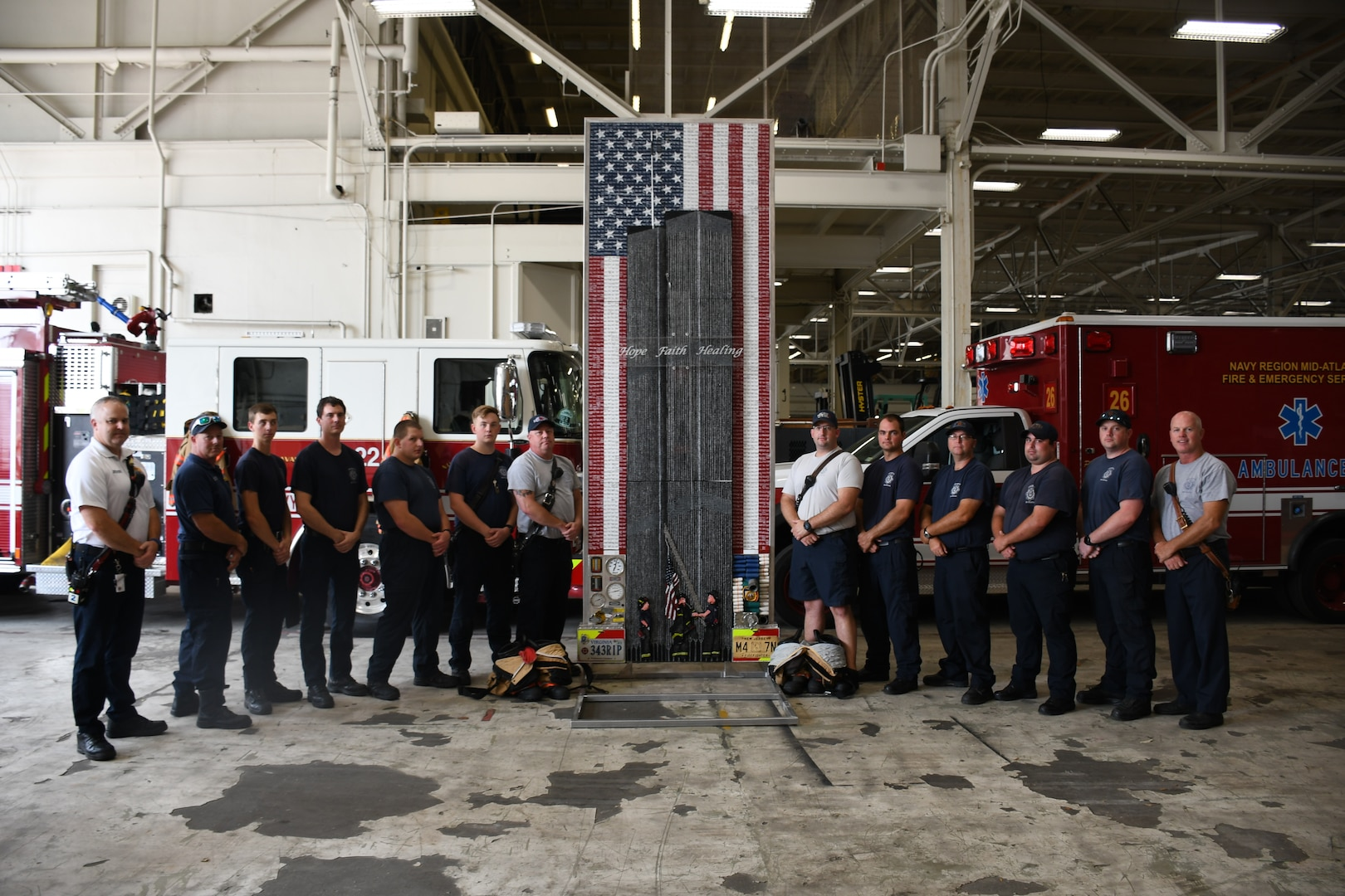 Members of the Navy Region Mid-Atlantic Fire and Emergency Services along with the Sept. 11 memorial tribute artwork designed by NNSY's SurgeMain Sailor, Machinist Mate Chief Petty Officer (MMC) Joseph Pisano . The tribute piece is made up of 30,000+ drywall and trim screws, 2,978 one-inch wooden blocks, the base, a simulated fire truck, is constructed of authentic gauges, cranks, handles, hoses, chevrons, and plates from a decommissioned fire truck and it stands 12 foot tall by four foot wide.