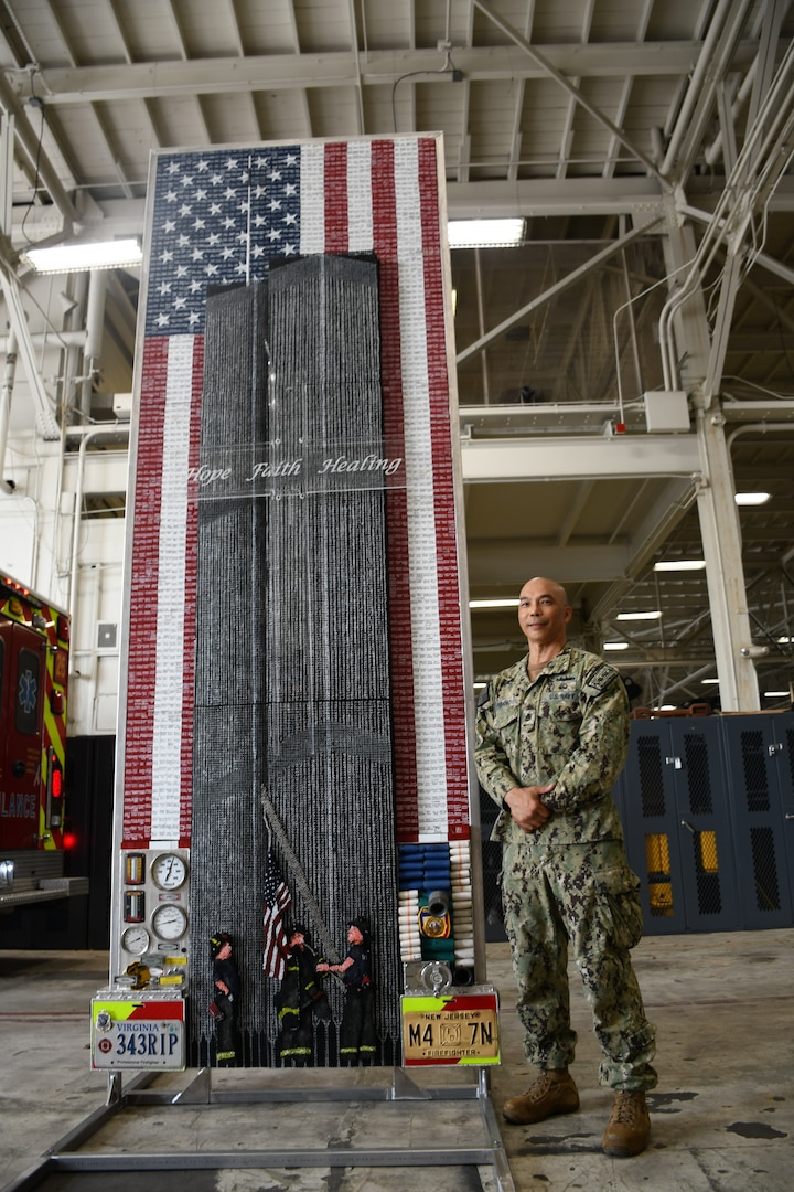 """Machinist Mate Chief Petty Officer (MMC) Joseph Pisano stands by his creation of the 9/11 memorial tribute piece called """"Divinity Among Heroes."""" The tribute piece is made up of 30,000+ drywall and trim screws, 2,978 one-inch wooden blocks, the base, a simulated fire truck, is constructed of authentic gauges, cranks, handles, hoses, chevrons, and plates from a decommissioned fire truck and it stands 12 foot tall by four foot wide."""