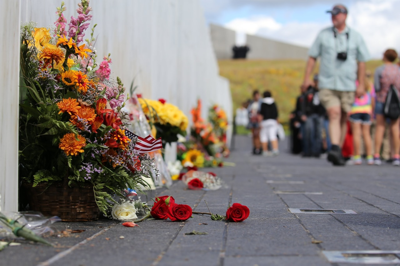 Visitors walk along a memorial wall adorned with flower bouquets.