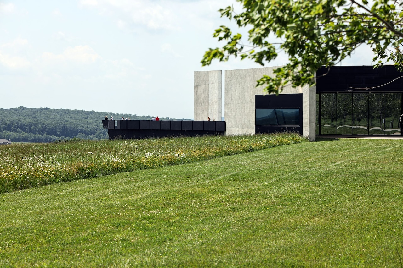 A memorial visitor center sits in the middle of a green field.