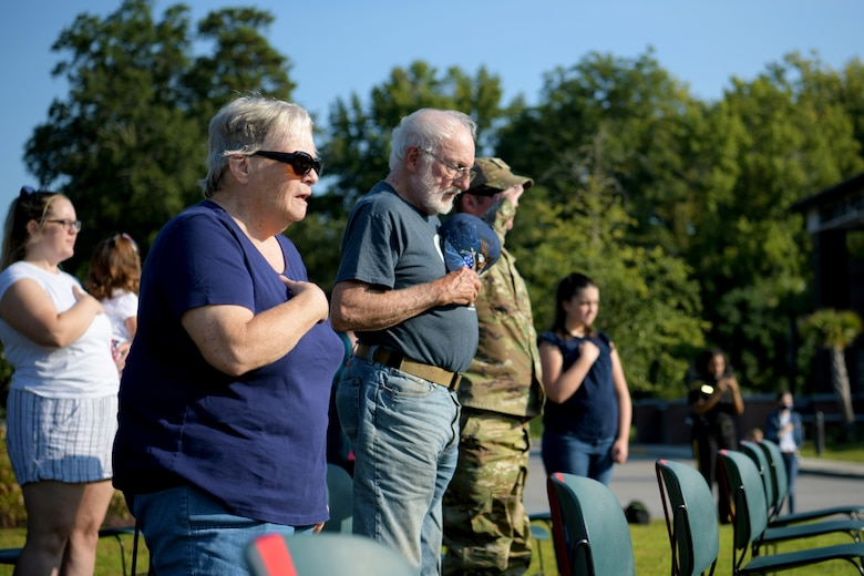 Susan Scouten, a resident of Sumter, left, sings along to the national anthem during a 9/11 memorial ceremony in Sumter, S.C., Sept. 11, 2021. The ceremony was held in remembrance of the 20th anniversary of the Sept. 11, 2001, attacks across the United States. (U.S. Air Force photo by Staff Sgt. K. Tucker Owen)
