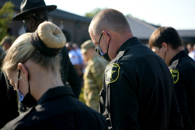Members of the Sumter County Sheriff's Department bow their heads for prayer during a 9/11 memorial ceremony in Sumter, S.C., Sept. 11, 2021. The ceremony was held in remembrance of the 20th anniversary of the Sept. 11, 2001, attacks across the United States. (U.S. Air Force photo by Staff Sgt. K. Tucker Owen)