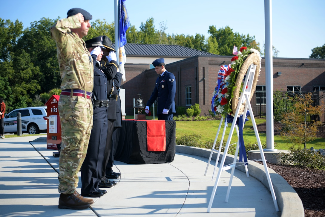 Members of a joint honor guard from Sumter first responders and Royal Air Force salute wreaths while an Airman assigned to the 20th Civil Engineer Squadron rings a bell during a 9/11 memorial ceremony in Sumter, S.C., Sept. 11, 2021. The ceremony was held in remembrance of the 20th anniversary of the Sept. 11, 2001, attacks across the United States. (U.S. Air Force photo by Staff Sgt. K. Tucker Owen)