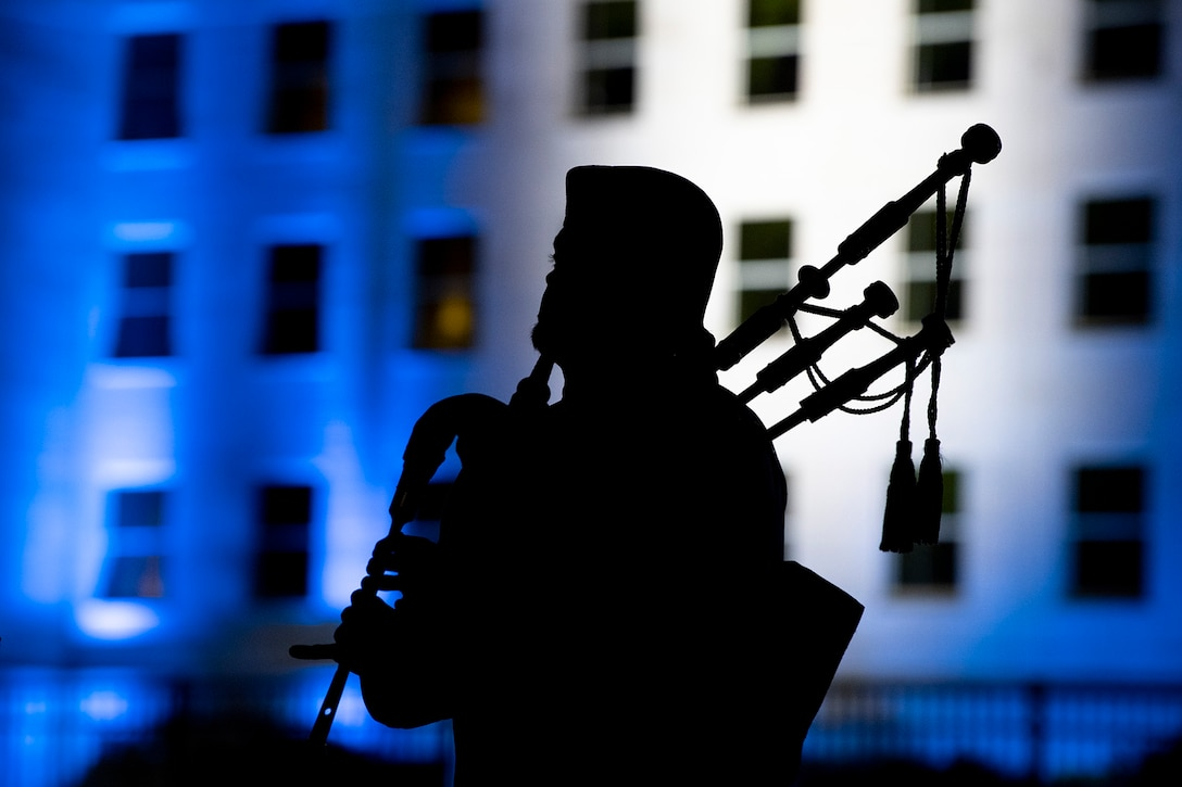 The silhouette of a bagpipe player in front of the Pentagon.