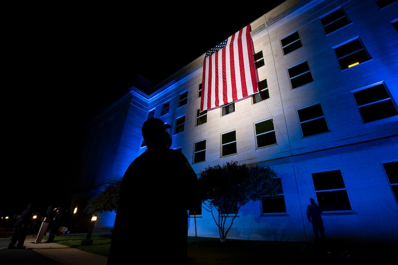 The silhouette of a man standing in front of the Pentagon with a large American flag unfurled down the side of the building.