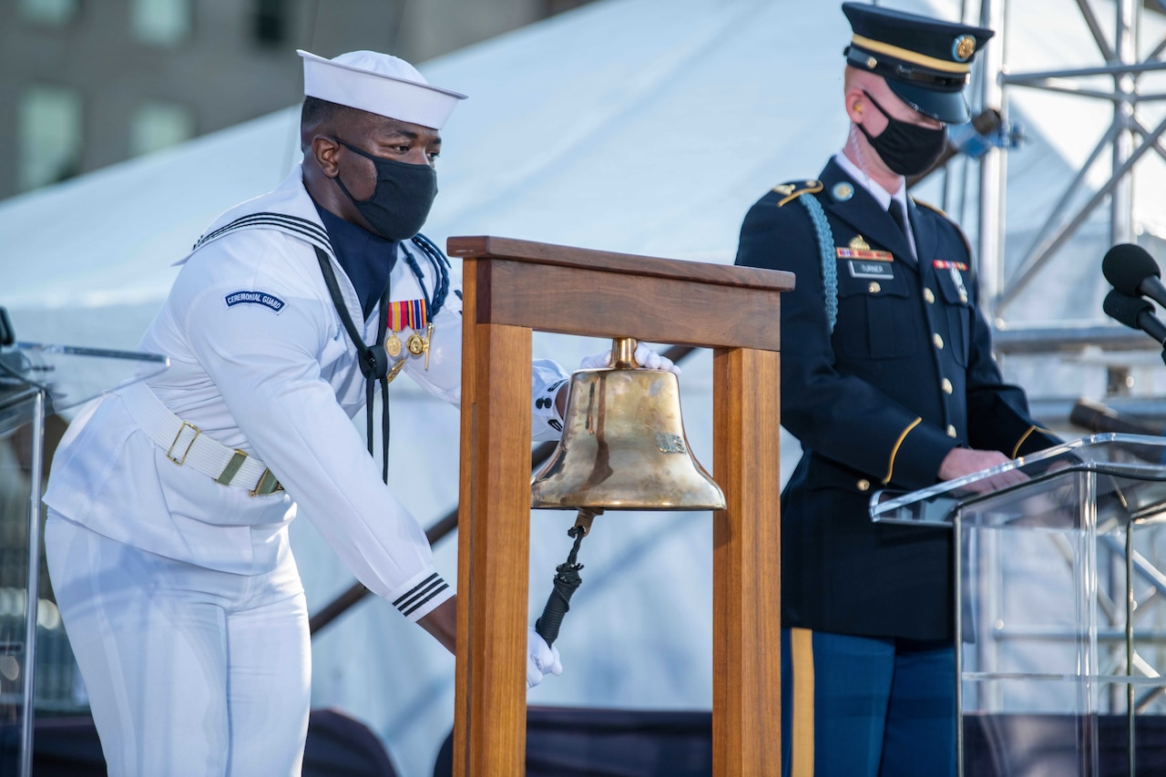 A sailor rings a bell while a soldier reads from a lectern.