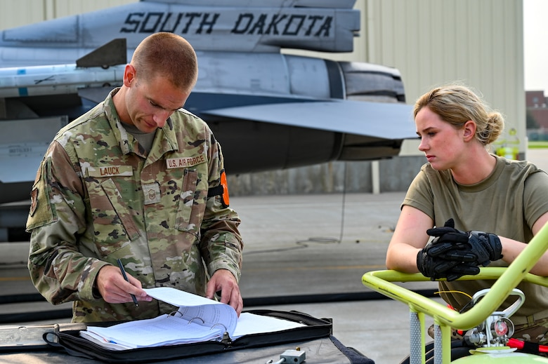 Master Sgt. Andrew Lauck and Staff Sgt. Mikayla Wilson, 114th Fighter Wing crew chiefs, review maintenance checklists prior to daily training during the 2021 Readiness Exercise at Joe Foss Field, Aug. 5.