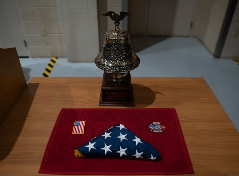 An American flag, patch, Cannon Air Force Base fire emergency services patch and ceremonial bell form part of a memorial to 9/11 during a ceremony at Cannon Air Force Base, N.M., Sep. 11, 2021. The memorial marked the 20th anniversary since the terrorist attacks on the United States in 2001 and included a nine-story stair climb in honor of the first responders who lost their lives responding to the attacks. (U.S. Air Force photo by Senior Airman Christopher Storer)