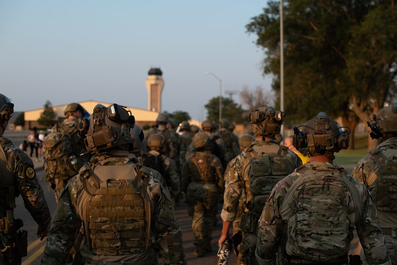 Members of the 27th Special Operations Security Forces Squadron walk to the Cannon Air Force Base Air Traffic Control tower during a 9/11 memorial ceremony at Cannon AFB, N.M., Sep. 11, 2021. The ceremony was dedicated to the first responders who lost their lives responding to the terrorist attacks on the United States 20 years ago. Participants carried names of the deceased up nine flights of stairs, where the names were hung on a dedicated stand. (U.S. Air Force photo by Senior Airman Christopher Storer)