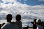 """Military family members and friends attending the Thunder Over New Hampshire Airshow Open House watch as the  United States Air Force Air Demonstration Squadron """"Thunderbirds"""" perform aerial maneuvers,  Pease Air National Guard Base, Portsmouth, New Hampshire, Sept. 10, 2021. Sept. 10 was military family day, where military family members and friends could see the air show performances before opening to the wider public. (U.S. Army National Guard photo by Devin Bard)"""