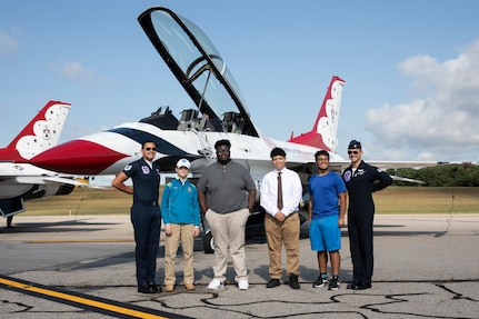 """(From left to right) Tech Sgt. Peter Rivera, United States Air Force Air Demonstration Squadron """"Thunderbirds"""", Zachory Durham, Tyler Harris, James Connolly, Max Saravia, and Maj. Michael Brewer, United States Air Force Air Demonstration Squadron """"Thunderbirds"""", pose for a photo at the 2021 Thunder Over New Hampshire Airshow Open House on Pease Air National Guard Base, Portsmouth, New Hampshire, Sept. 10, 2021. Brewer and Rivera gave a tour of their F-16 Fighting Falcon to a small group of people before starting their aerial performance show. (U.S. Army National Guard photo by Devin Bard)"""